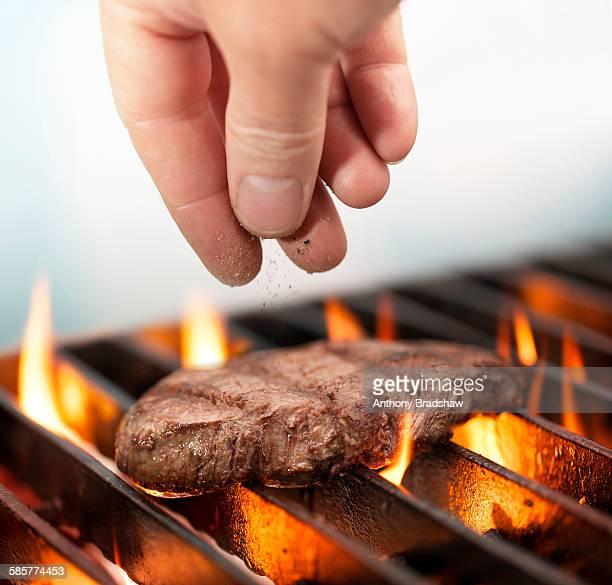 Seasoning steak on a barbeque