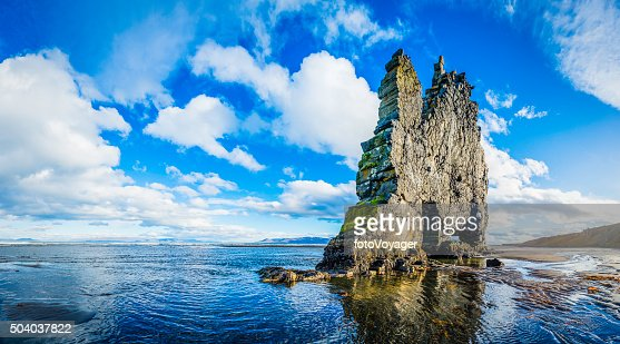Seastack on ocean beach beneath big sky panorama Hvitserkur Iceland