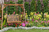 Wooden swing seat in flower garden