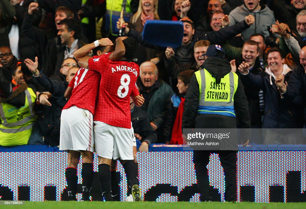 A seat is thrown onto the pitch as Nani of Manchester United celebrates scoring to make it 23 next to a safety steward