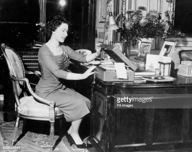 Seated at her desk in Buckingham Palace the Queen opens one of her boxes in which documents and papers which have been sorted for her attention are...