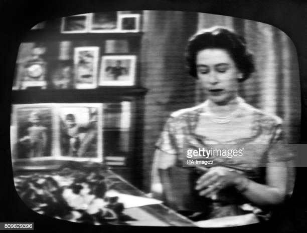 Seated at her desk in the Long Library at Sandringham with portraits of her children and Christmas cards forming a homely background the Queen is...