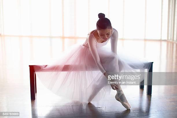 Seated ballerina adjusting her ballet shoes