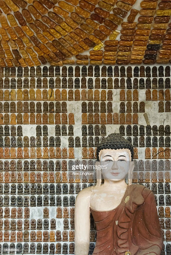 Seated Buddha surrounded by little Buddha tiles : Stock Photo