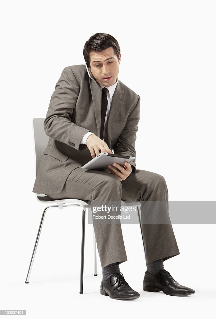 Seated business man using tablet and phone : Stock Photo