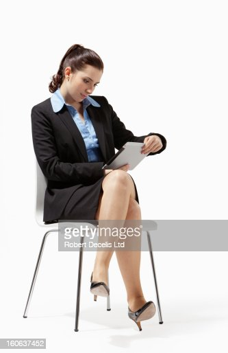 Seated business woman reading tablet : Stock Photo