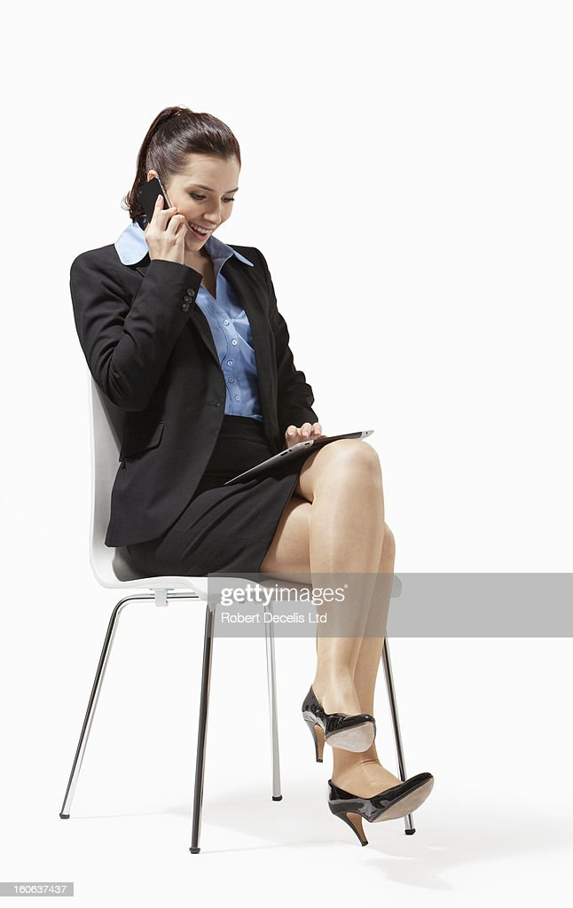 Seated business woman using smart phone : Stock Photo