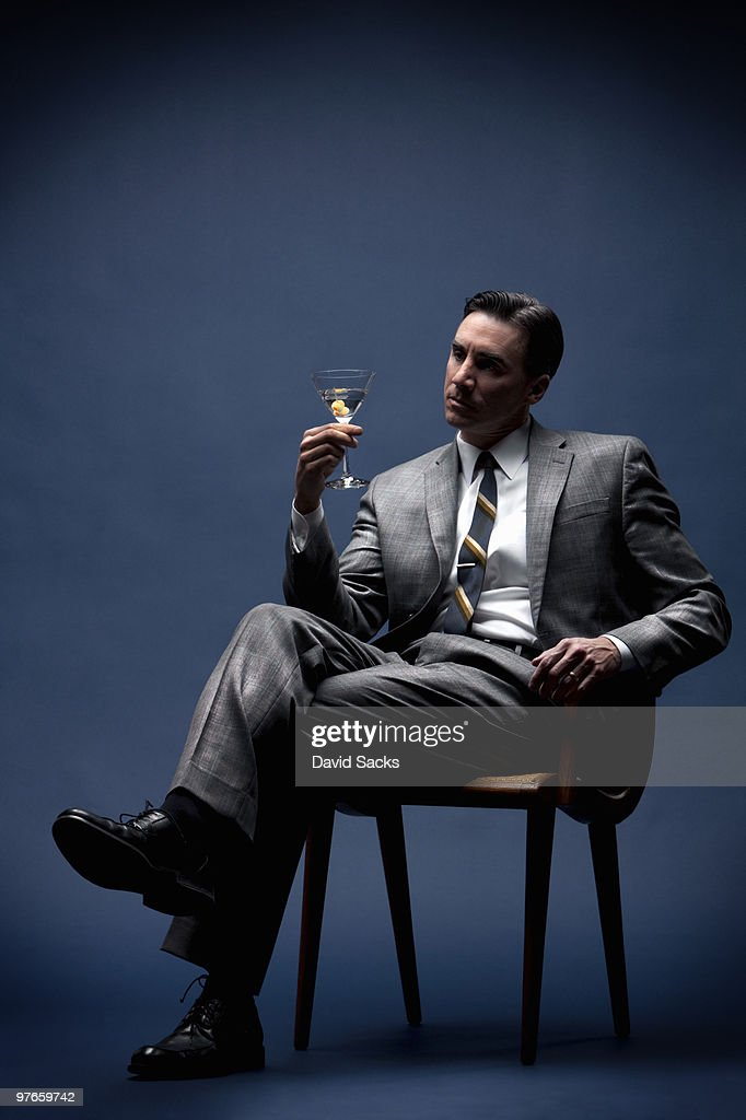 Seated man in business suit holding martini : Stock Photo