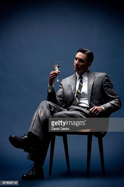 Seated man in business suit holding martini