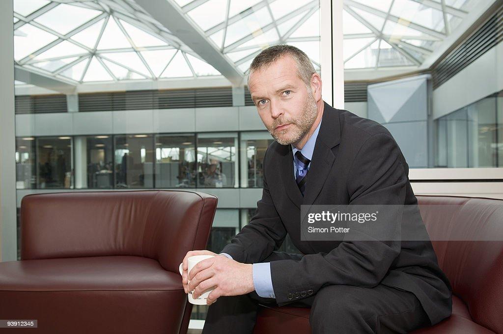 A seated senior business man : Stock Photo