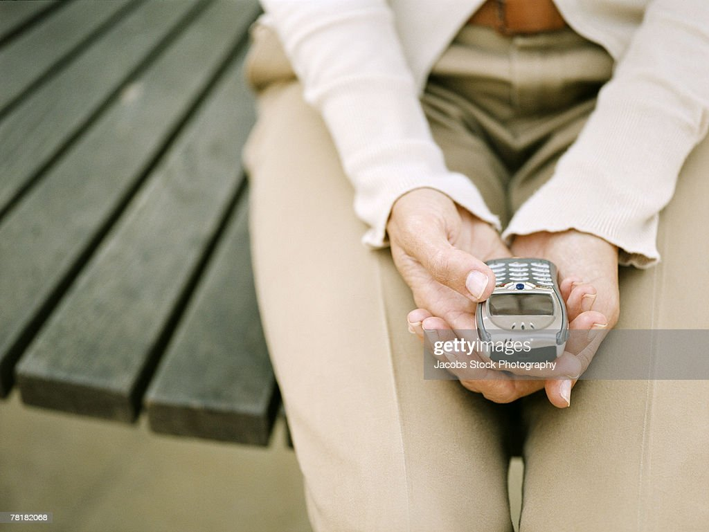 Seated woman holding a mobile phone : Stock Photo