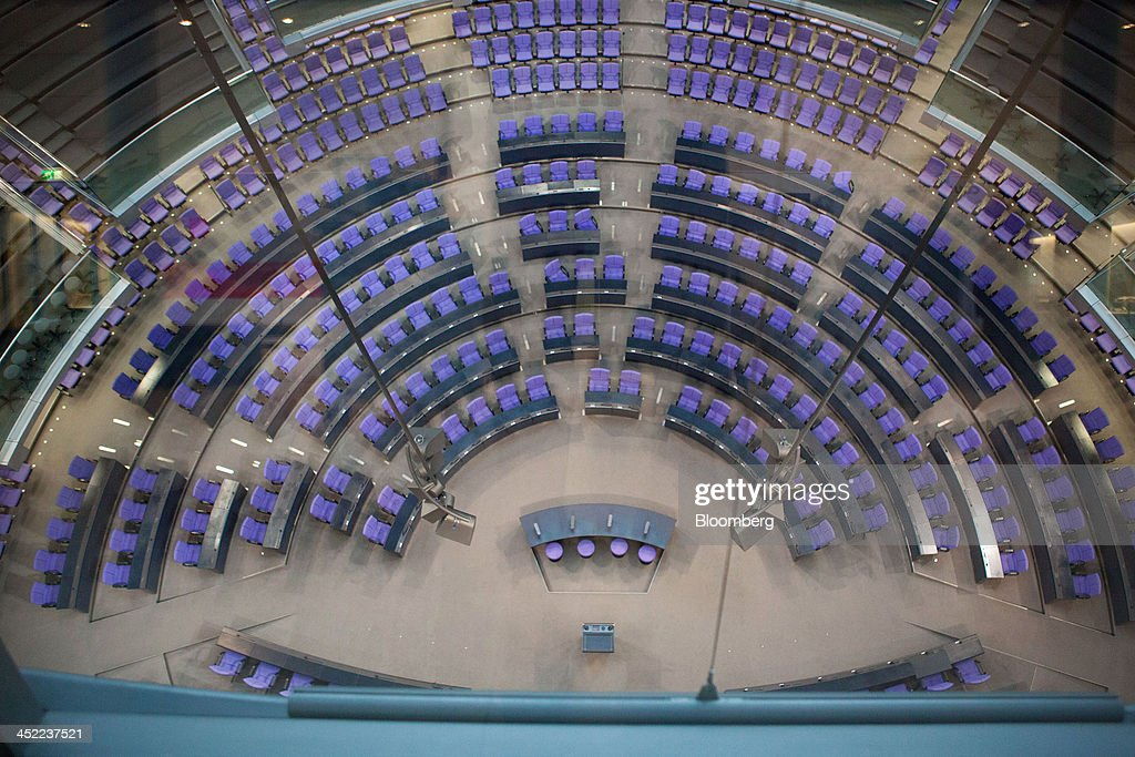 Seats sit empty in the plenary hall of the German parliament building, or Reichstag, as a coalition agreement between the Christian Democratic Union and the Social Democratic Party is reached in Berlin, Germany, on Wednesday, Nov. 27, 2013. German Chancellor Angela Merkel reached an agreement with the Social Democrats on a coalition that would implement a national minimum wage and increase spending on pensions and infrastructure without raising taxes. Photographer: Krisztian Bocsi/Bloomberg via Getty Images