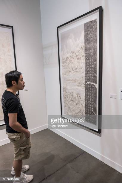 Seattle Art Fair attendee examines the work 'Houshan Revolve' by Wang Tiande at CenturyLink Field on August 6 2017 in Seattle Washington