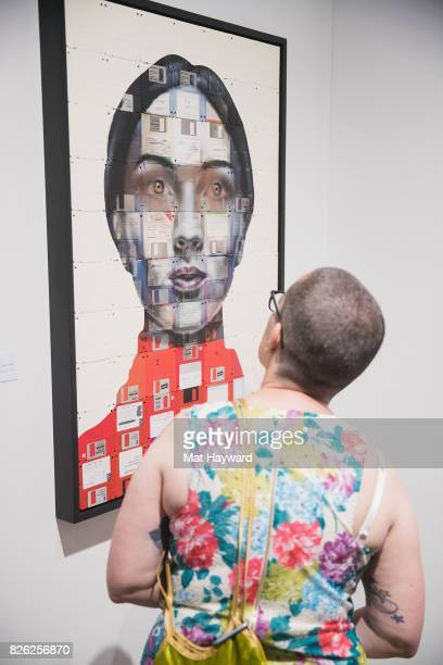 Seattle Art Fair attendee views an original work of art created on wood with used floppy disks and oil paint created by British artist Nick Gentry at...