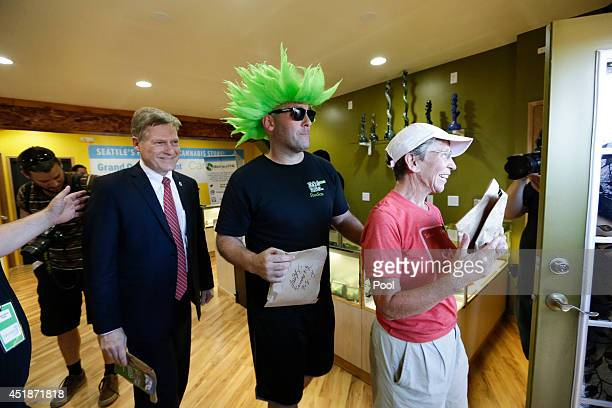 Seattle City Attorney Pete Holmes Jeremy Cooper and first customer Deb Greene exit after purchasing marijuana at the Cannabis City retail marijuana...