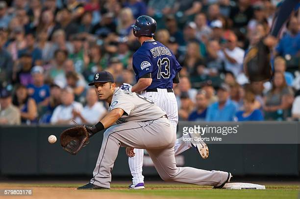 Seattle Mariners first baseman Jesus Montero takes the throw but is too late to force out Colorado Rockies center fielder Drew Stubbs during a...