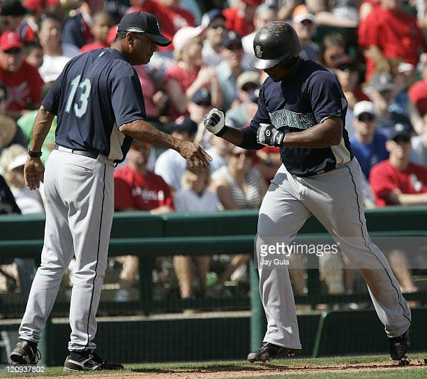 Seattle Mariners Jose Guillen is congratulated by 3rd base coach Carlos Garcia after hitting a HR in Cactus League action vs the LA Angels at Tempe...