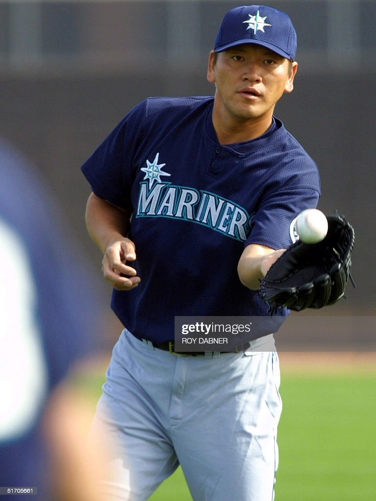 Seattle Mariners pitcher Kazuhiro Sasaki catches a ball thrown by teammate Paul Abbott as the two warm up during the first day of Spring Training...
