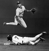 Seattle Mariners player Rey Quinones top jumps over Boston Red Sox player Spike Owens to throw the ball to first base during a game at Fenway Park in...