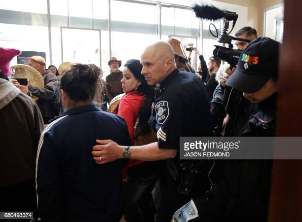 A Seattle police officer makes his way through a crowd of indigenous leaders and climate activists as they disrupt business at a Chase Bank branch to...