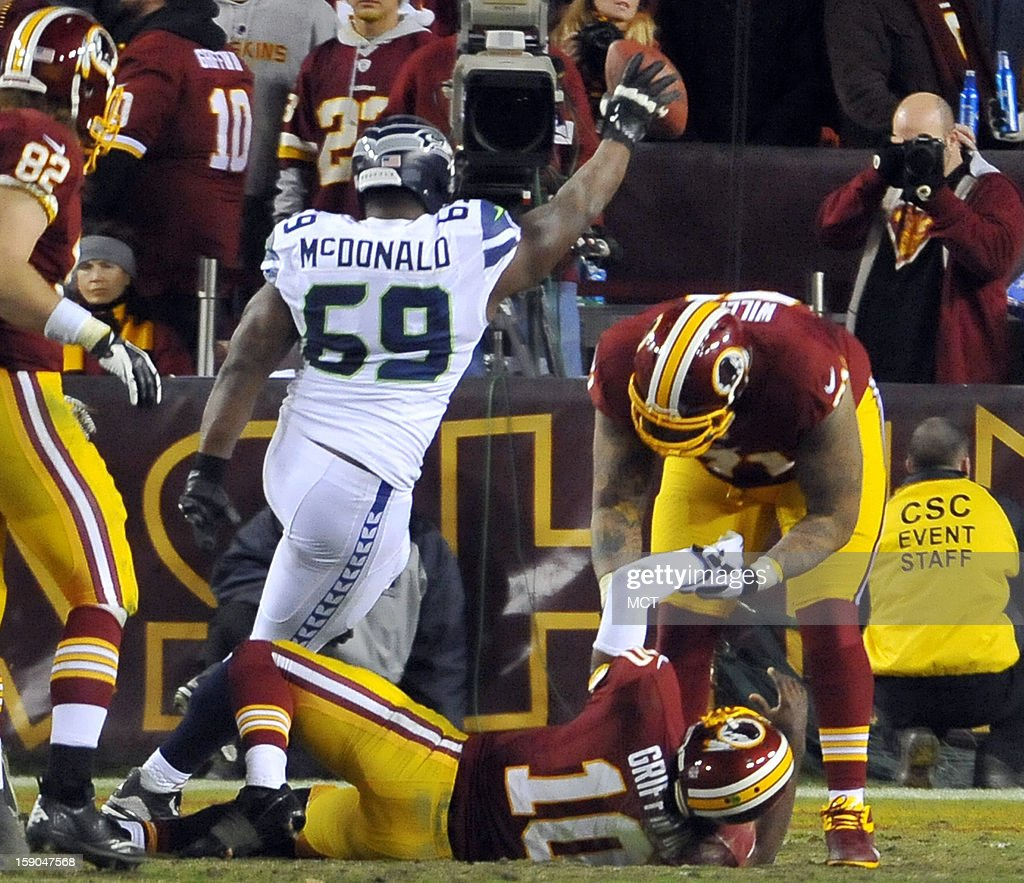 Seattle Seahawks defensive tackle Clinton McDonald (69) celebrates a fumble recovery as Washington Redskins quarterback Robert Griffin III (10) lies on the turf with a leg injury in the fourth quarter of an NFC wild-card playoff game at FedEx Field in Landover, Maryland, Sunday, January 6, 2012. The Seahawks defeated the Redskins, 24-14.