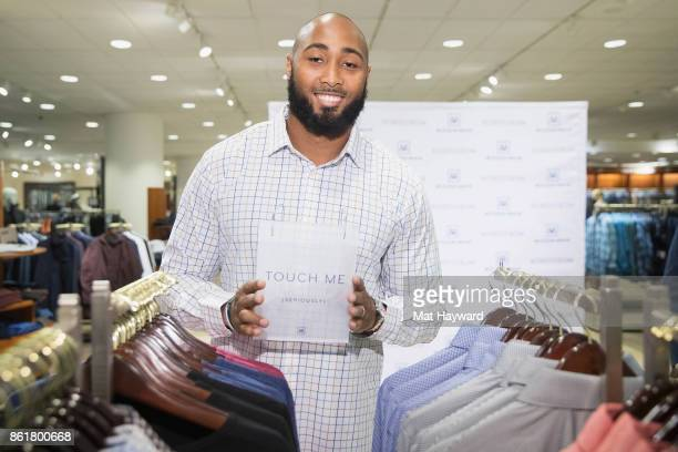 Seattle Seahawks linebacker KJ Wright holds a MizzenMain 'Touch Me' sign at Nordsrom on October 15 2017 in Seattle Washington