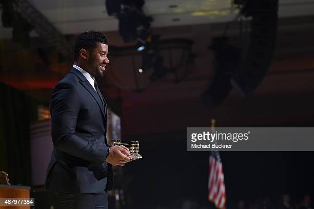 Seattle Seahawks quarterback Russell Wilson accepts an award onstage during Muhammad Ali's Celebrity Fight Night XXI at the Jw Marriott Phoenix...