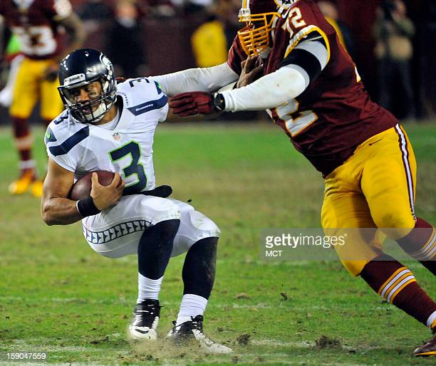 Seattle Seahawks quarterback Russell Wilson fends off Washington Redskins defensive end Stephen Bowen in the fourth quarter of an NFC wildcard...