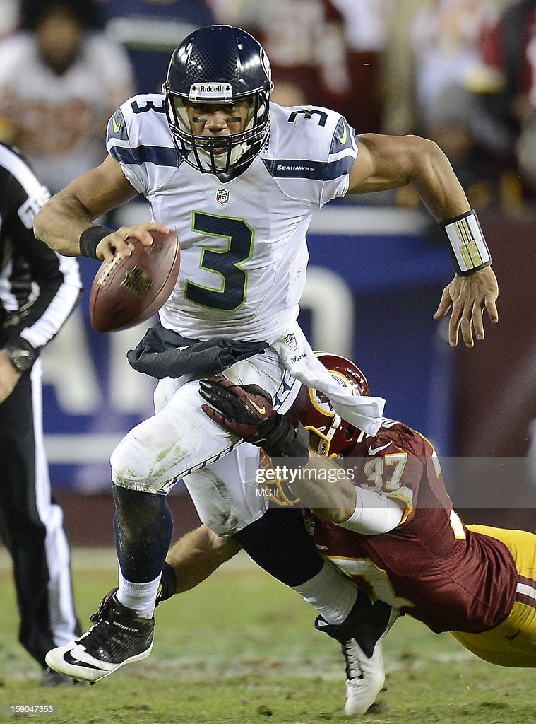 Seattle Seahawks quarterback Russell Wilson (3) gets sacked by Washington Redskins strong safety Reed Doughty (37) in the fourth quarter of an NFC wild-card playoff game at FedEx Field in Landover, Maryland, Sunday, January 6, 2013. The Seahawks defeated the Redskins, 24-14.