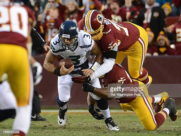 Seattle Seahawks quarterback Russell Wilson goes down for a ten yard loss as he is sacked by Washington Redskins defensive end Stephen Bowen top and...