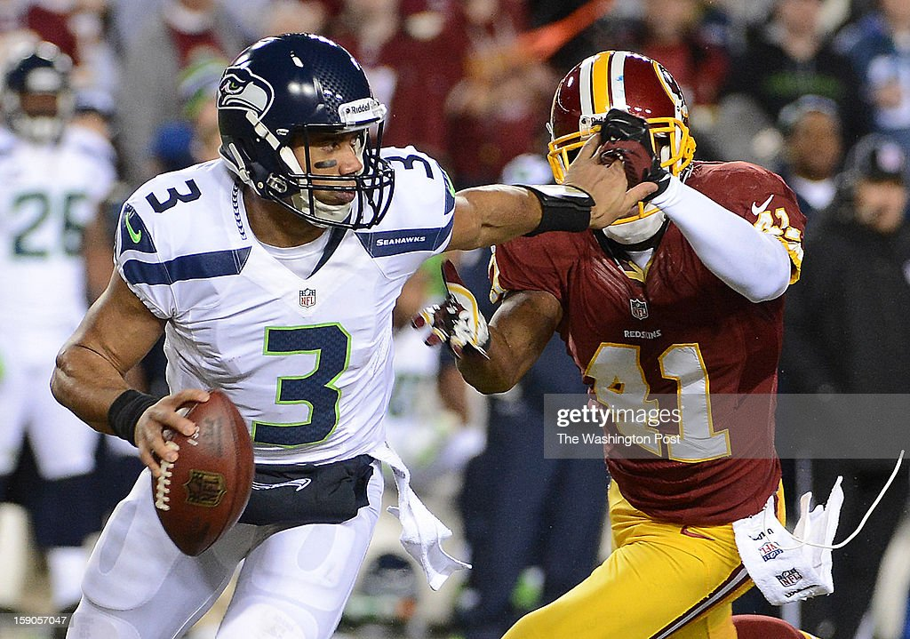 Seattle Seahawks quarterback Russell Wilson (3) grabs a hold of Washington Redskins free safety Madieu Williams' (41) face mask as he scrambles in the second quarter of the first round NFC playoff game between the Washington Redskins and the Seattle Seahawks at FedEd Field in Landover, Md., on Sunday, January 6, 2013.