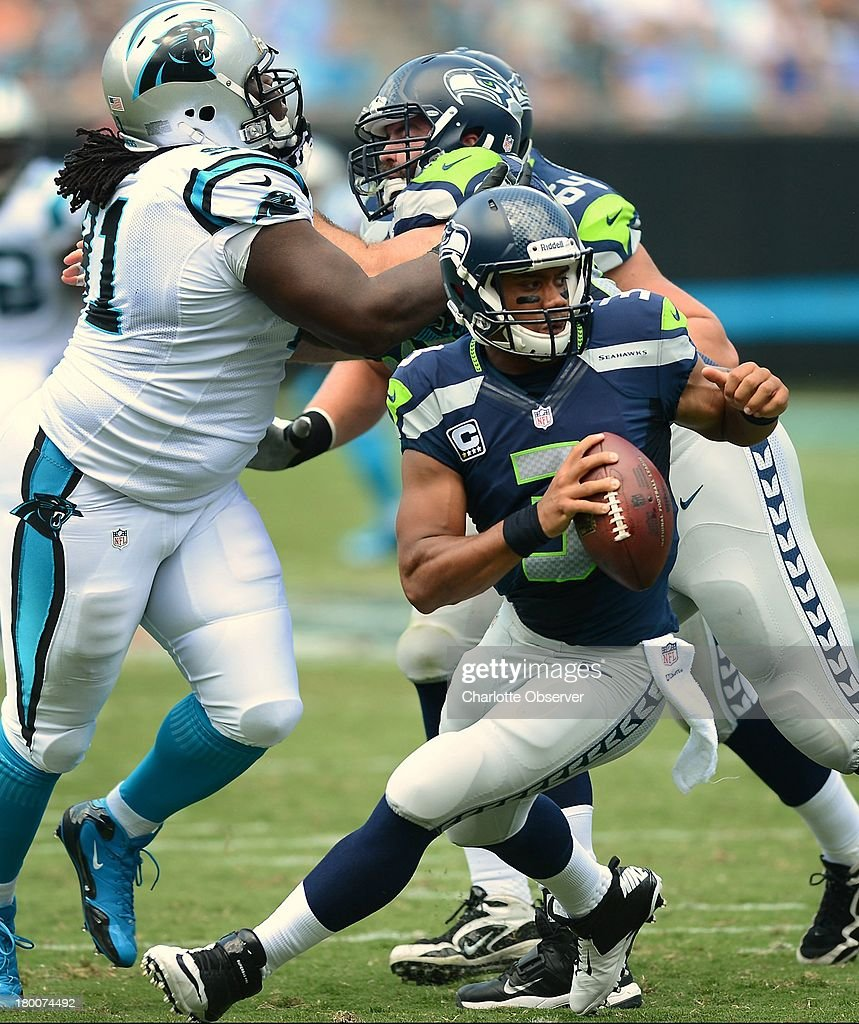 Seattle Seahawks quarterback Russell Wilson (3) scrambles around the pocket as Seahawks guard J.R. Sweezy (64) fights off Carolina Panthers defensive tackle Colin Cole (91) during first-quarter action at Bank of America Stadium in Charlotte, North Carolina, on Sunday, September 8, 2013. Seattle won, 12-7.