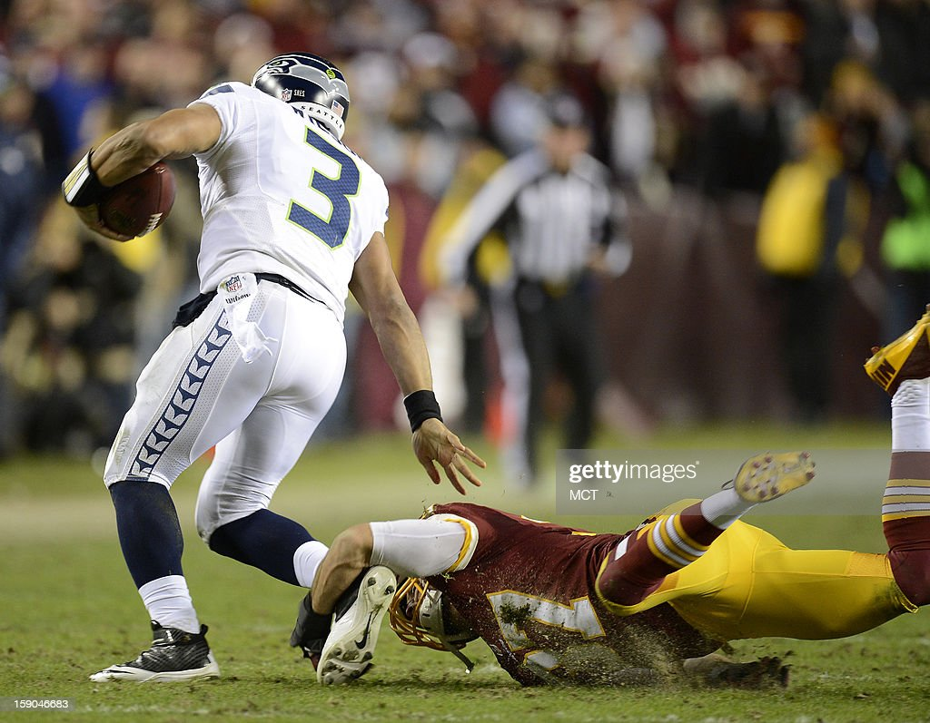 Seattle Seahawks quarterback Russell Wilson (3) slips a tackle attempt by Washington Redskins strong safety Reed Doughty (37), while scrambling in the third quarter of an NFC wild-card playoff game at FedEx Field in Landover, Maryland, Sunday, January 6, 2013.