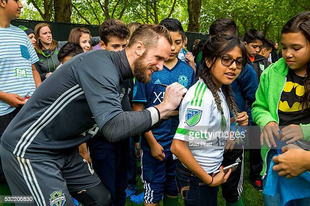Seattle Sounders FC goalkeeper Stefan Frei with a local art student from Voyager Middle School at 'The Fabric of Sounders FC' design project uniting...