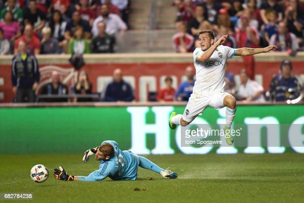 Seattle Sounders forward Jordan Morris jumps over Chicago Fire goalkeeper Matt Lampson after blocking a goal in the first half during a game against...