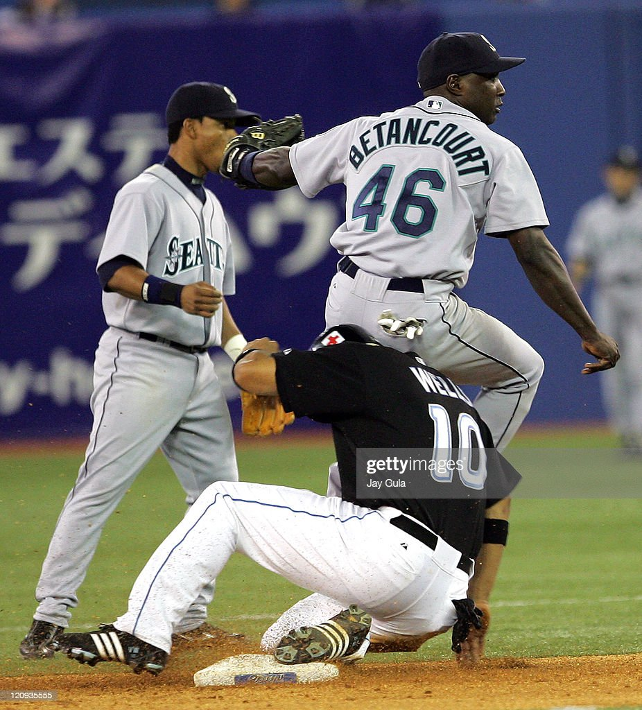 Seattle SS Yuniesky Betancourt comes down on the shoulder of Vernon Wells after his relay to 1st base was not in time to get a double play at Rogers...