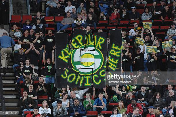 Seattle SuperSonics fans hold up signs in support of keeping the SuperSonics franchise in Seattle for the upcoming season during the game against the...