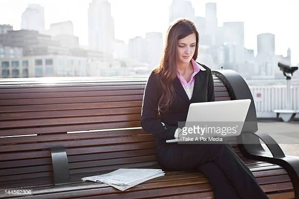 USA, Seattle, Young businesswoman working on laptop on bench