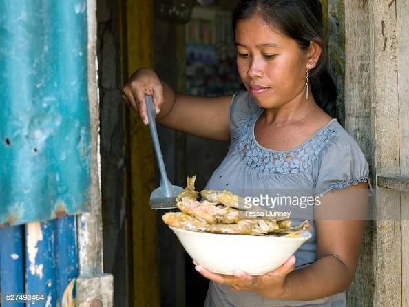 Seaweed farmer Marissa Gegante holding a bowl of freshly caught and cooked fried fish for lunch in Tamiao Bantayan Island The Philippines On November...