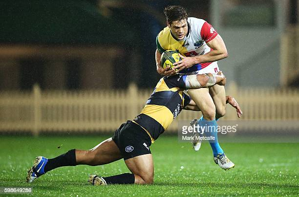 Seb Wileman of the Rays is tackled by Ben Tapuai of the Spirit during the round two NRC match between the Sydney Rays and the Perth Spirit at North...
