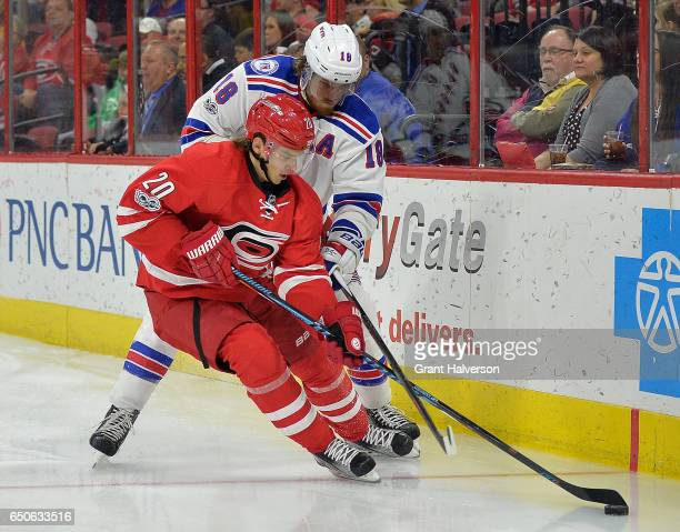 Sebastian Aho of the Carolina Hurricanes and Marc Staal of the New York Rangers vie for the puck during the game at PNC Arena on March 9 2017 in...