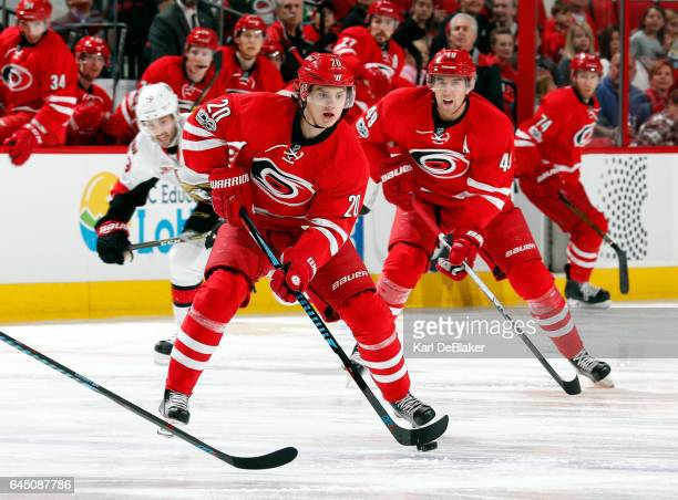 Sebastian Aho of the Carolina Hurricanes carries the puck into the neutral zone trailed by Victor Rask during an NHL game against the Ottawa Senators...