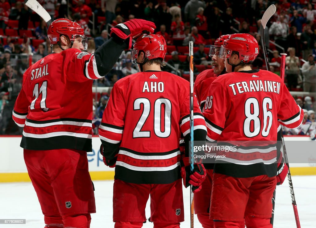 Sebastian Aho #20 of the Carolina Hurricanes celebrates his first-period powerplay goal against the New York Rangers with teammates Jordan Staal #11, Teuvo Teravainen #86 and Justin Faulk #27 during an NHL game on November 22, 2017 at PNC Arena in Raleigh, North Carolina.
