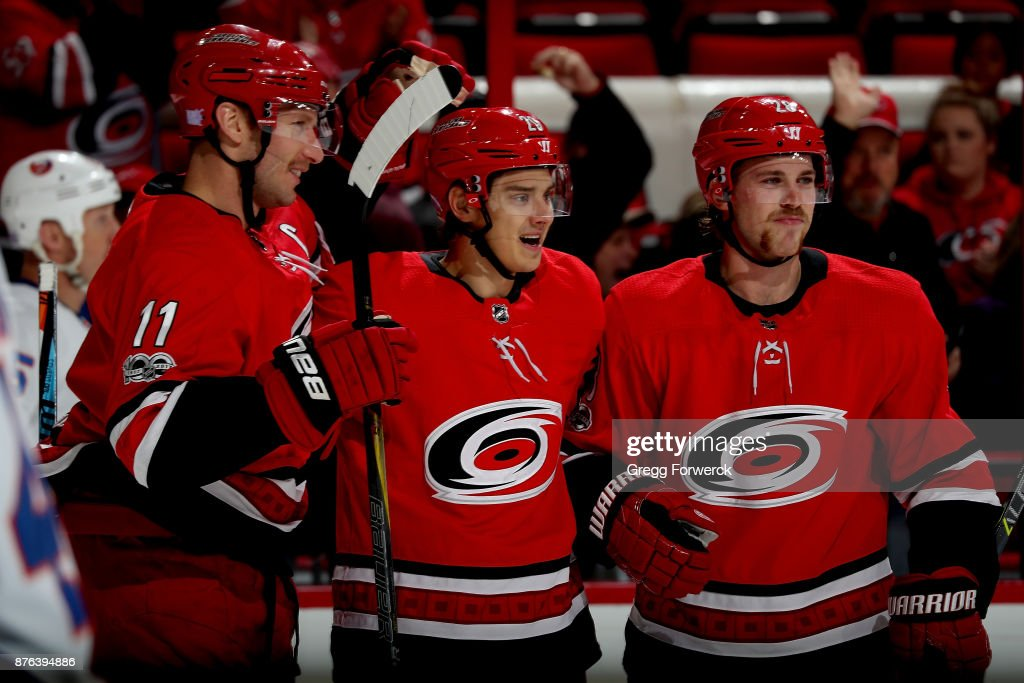 Sebastian Aho #20 of the Carolina Hurricanes celebrates with teammates after scoring a goal during an NHL game against the New York Islanders on November 19, 2017 at PNC Arena in Raleigh, North Carolina.