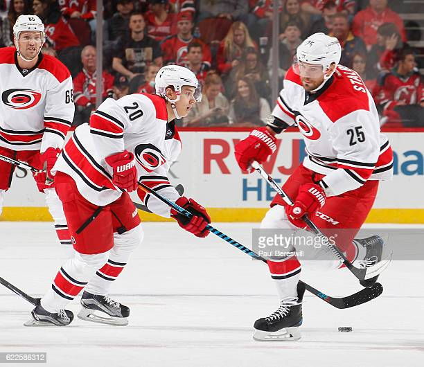 Sebastian Aho of the Carolina Hurricanes circles at center ice with the puck as he skates around teammates in an NHL hockey game against the New...