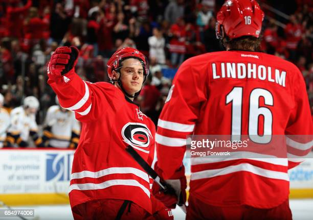 Sebastian Aho of the Carolina Hurricanes congratulates teammate Elias Lindholm on his empty net goal during an NHL game against the Nashville...