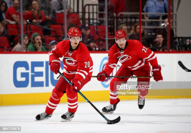 Sebastian Aho of the Carolina Hurricanes gets out on a break and carries the puck as teammate Brett Pesce skates close behind during an NHL game...