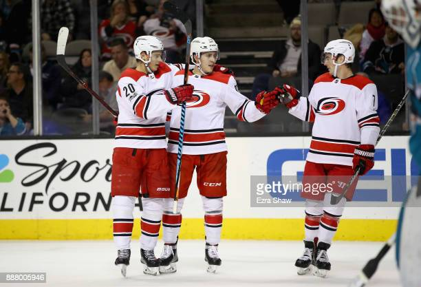 Sebastian Aho of the Carolina Hurricanes is congratulated by Teuvo Teravainen and Derek Ryan after he scored on Martin Jones of the San Jose Sharks...