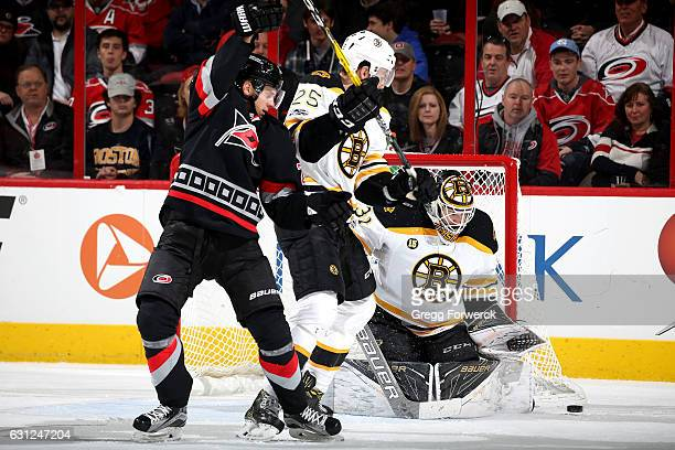 Sebastian Aho of the Carolina Hurricanes looks to disrupt Brandon Carlo of the Boston Bruins as Zane McIntyre makes the save during an NHL game on...