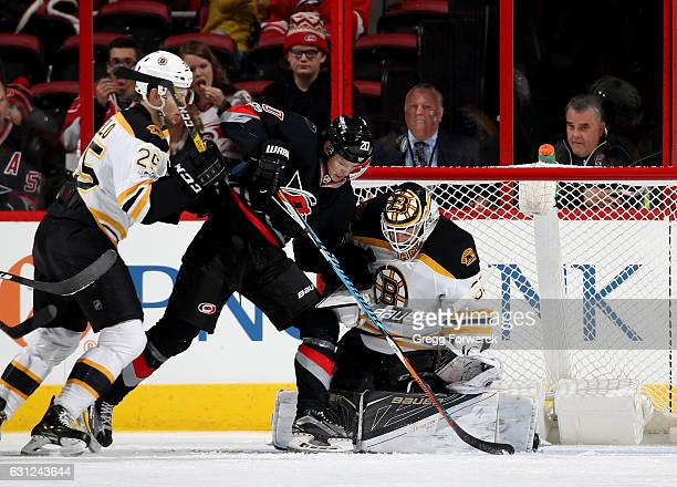 Sebastian Aho of the Carolina Hurricanes looks to jam the puck in the net as Zane McIntrye of the Boston Bruins goes down in the crease and Brandon...